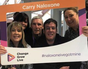 Naloxone activists pose with a sign